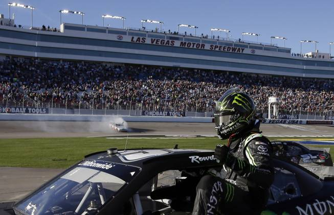 Kyle Busch exits his car after finishing second to Brad Keselowski, doing a burnout at rear, in the NASCAR Nationwide Series auto race Saturday, March 8, 2014, in Las Vegas.