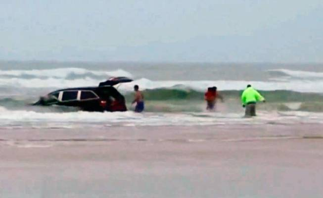 In this image made from video and released by Simon Besner, lifeguards rescue children from a minivan that their mother drove into the Atlantic Ocean on Tuesday, March 4, 2014, in Daytona Beach, Fla. Ebony Wilkerson, 31, a pregnant South Carolina woman who drove a minivan carrying her three young children into the ocean surf off Florida had talked about demons before leaving the house, according to her sister.
