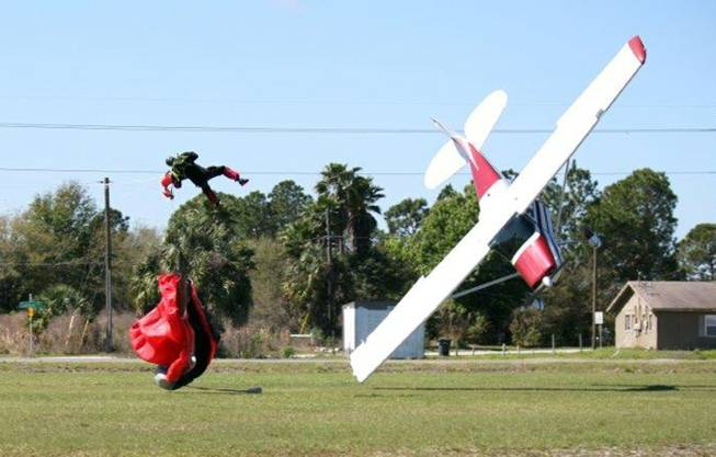 This photo released by the Polk County Sheriff's Office shows a plane nose-diving into the ground after getting tangled with a parachutist, left, Saturday, March 8, 2014, at the South Lakeland Airport in Mulberry, Fla. Both the pilot and jumper were hospitalized with minor injuries.