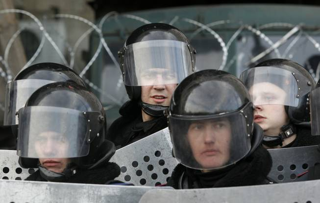 Ukrainian riot police stand at the entrance of the regional administrative building during a pro-Russia rally in Donetsk, Ukraine, on Saturday, March 8, 2014. Pro-Russian activists continued to gather on Saturday in the eastern Ukrainian city of Donetsk, as Russia was reported to be reinforcing its military presence in Crimea.