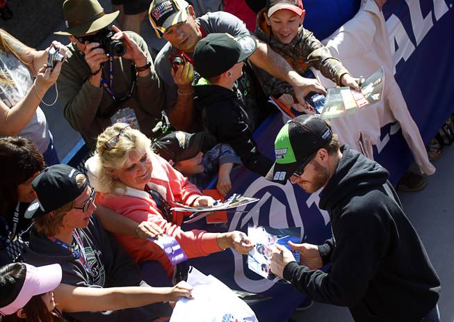Dale Earnhardt Jr. signs autographs after a drivers meeting before the Kobalt 400 NASCAR Sprint Cup Series race at the Las Vegas Motor Speedway Sunday, March 9, 2014. Earnhardt was leading the race on the final lap but ran out of fuel and was passed by Brad Keselowski.
