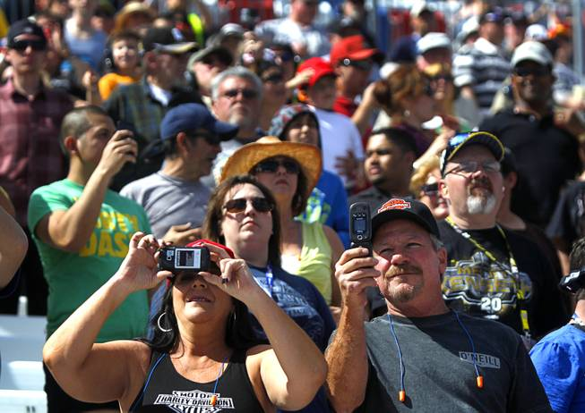 A couple takes video on their phones during the Kobalt 400 NASCAR Sprint Cup Series race at the Las Vegas Motor Speedway Sunday, March 9, 2014.