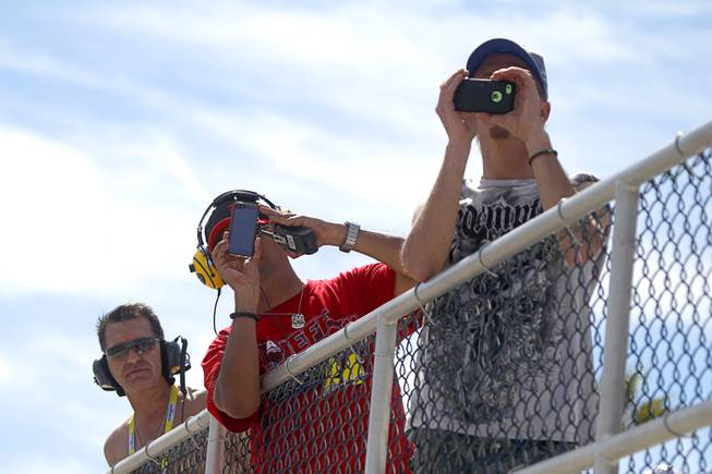 Fans take video on their phones during the Kobalt 400 NASCAR Sprint Cup Series race at the Las Vegas Motor Speedway Sunday, March 9, 2014.