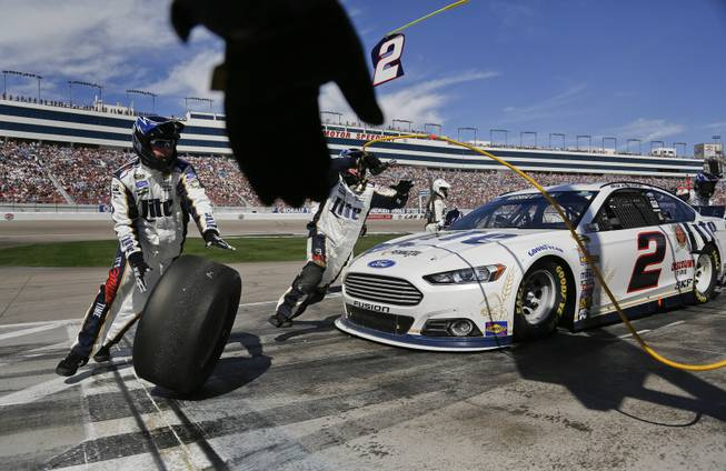 A pit crew member reaches to grab one of the used tires off of Brad Keselowski's car during a pit stop at a NASCAR Sprint Cup Series auto race on Sunday, March 9, 2014, in Las Vegas.