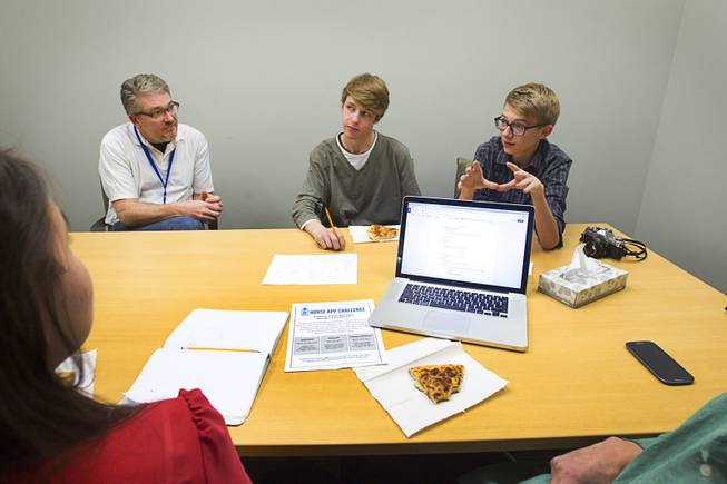 Mentor Tim Mooney, left, a senior director of retail product management for Zappos, listens to Connor Dougherty, center, and Zane Mechen, students at the Las Vegas Academy, during a workshop for first annual Congressional Science, Technology, Engineering and Math (STEM) Academic Competition, also known as the House App Contest, at Zappos in downtown Las Vegas Monday, March 10, 2014. The national contest for high school students, established by members of the U.S. House of Representatives in 2013, involves developing an app and creating a video demonstration to explain it.
