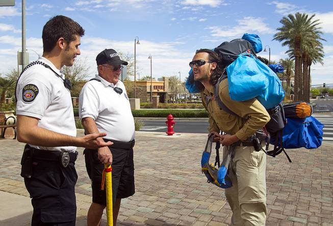 "The District security officers Atom Fogarty , left, and Carl Knoll talk with Robert Sorensen, 27, as he heads out for a walk from Henderson to Israel Monday, March 10, 2014. Sorensen said he is not a religious man but that it was a ""spiritual"" journey. Sorensen estimated the trip to be 16,500 miles."