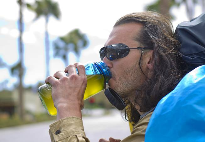 "Robert Sorensen, 27, stops for a drink as he heads out for a walk from Henderson to Israel Monday, March 10, 2014. Sorensen said he is not a religious man but that it was a ""spiritual"" journey. Sorensen estimated the trip to be 16,500 miles."