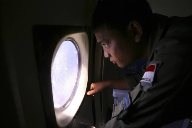 An Indonesian navy crew member scans the water bordering Indonesia, Malaysia and Thailand during a search operation for the missing Malaysian Airlines Boeing 777 near the Malacca straits on Monday, March 10, 2014.