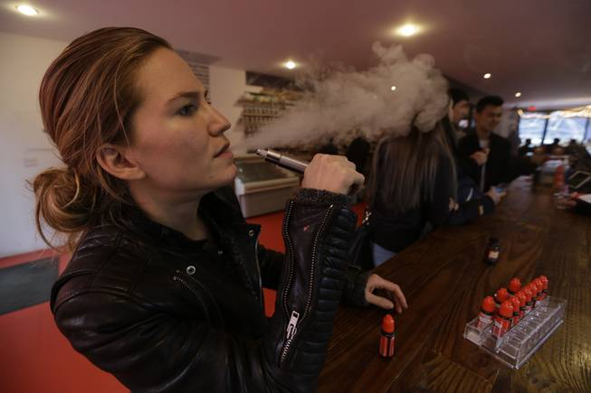 In this Feb. 20, 2014, photo, Talia Eisenberg, co-founder of the Henley Vaporium, uses her vaping device in New York.