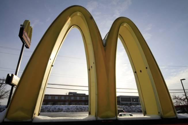In this Tuesday, Jan. 21, 2014, file photo, the McDonald's Golden Arches logo at a McDonald's restaurant is covered with snow in Robinson Township, Pa.