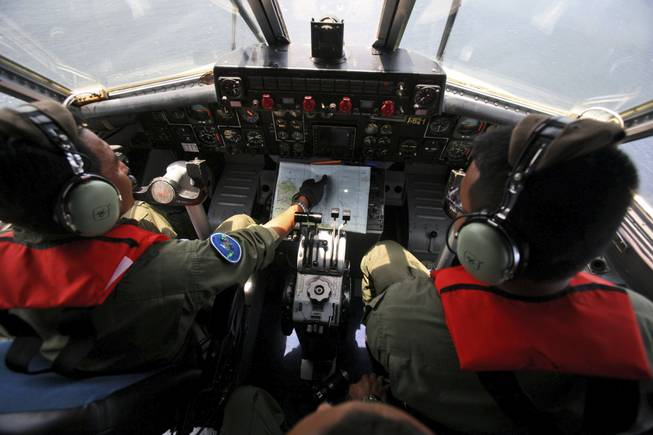 Indonesian navy pilots Maj. Bambang Edi Saputro, left, and 2nd Lt. Tri Laksono check their map during a search operation for the missing Malaysian Airlines Boeing 777 over the waters bordering Indonesia, Malaysia and Thailand near the Malacca straits on Monday, March 10, 2014.