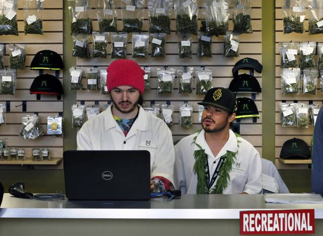 In this Jan. 1, 2014, file photo, employees Chris Broussard, left, and David Marlow, work behind sales counter inside Medicine Man marijuana retail store, which opened as a legal recreational retail outlet in Denver. Colorado made roughly $2 million in marijuana taxes in January, state revenue officials reported Monday, March 10, 2014, in the world's first accounting of the recreational pot business.