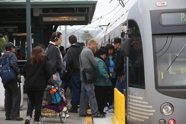 Pedestrians board a train at Union Station Friday March 7, 2014, in Los Angeles. Americans are boarding public buses, trains and subways in greater numbers than any time since the suburbs began to boom. Nearly 10.7 billion trips in 2013, to be precise, the highest number since 1956.