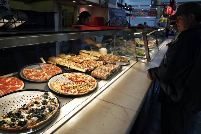 In this April 4, 2011, file photo, a customer looks at pizzas at Sbarro restaurant in San Jose, Calif. Sbarro said Monday, March 10, 2014, that it is filing for Chapter 11 reorganization, the struggling pizza chain's second trip through bankruptcy court in less than three years.