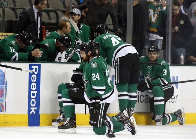 Dallas Stars right wing Alex Chiasson (12) bows his head on the bench as defenseman Jordie Benn (24) takes a knee on the ice after play was stopped in the first period of an NHL Hockey game against the Columbus Blue Jackets, Monday, March 10, 2014, in Dallas. Stars center Rich Peverly was taken to a hospital after a medical emergency.