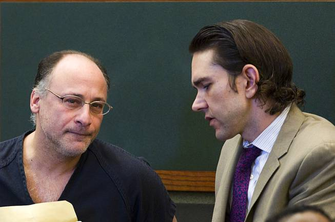 Mark Picozzi, left, listens to attorney Casey Landis before his  preliminary hearing at the Regional Justice Center Tuesday, March 11, 2014. Picozzi is accused of impersonating a police officer and forcing women working for escort services to perform sexual acts.