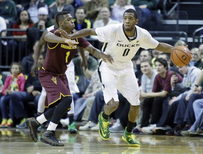 Oregon forward Mike Moser, right, dribbles against Arizona State guard Jahii Carson during the second half of an NCAA college basketball game in Eugene, Ore., Tuesday, March 4, 2014.  Moser led Oregon with 22 points and 17 rebounds as they beat Arizona State 85-78.