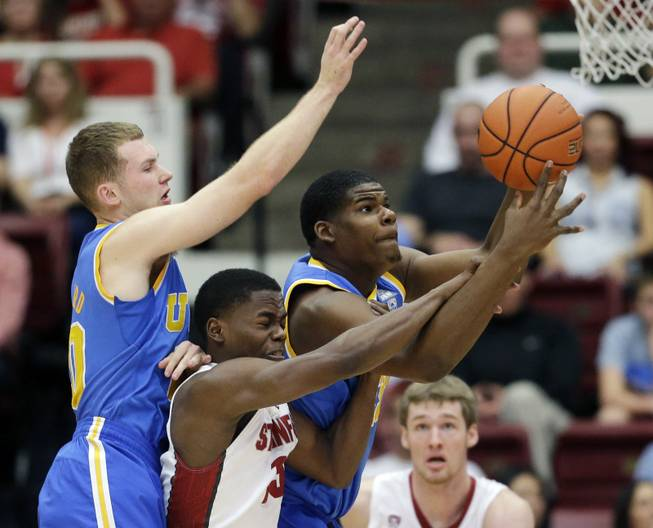 UCLA's Tony Parker, right, grabs a rebound next to Stanford guard Marcus Allen, center, and teammate Bryce Alford, left, during the first half of an NCAA college basketball game on Saturday, Feb. 22, 2014, in Stanford, Calif.