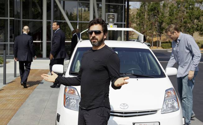Google co-founder Sergey Brin gestures after riding in a driverless car with California Gov. Edmund G. Brown Jr., left, and state Sen. Alex Padilla, second from left, to a bill signing for driverless cars at Google headquarters in Mountain View, Calif., Sept. 25, 2012.