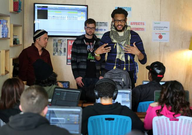 In this Monday, Feb. 10, 2014, photo, members of The Flobots and Youth on Record founders James Laurie, center, and Stephen Brackett, right, work with music students at Youth on Record headquarters in Denver.