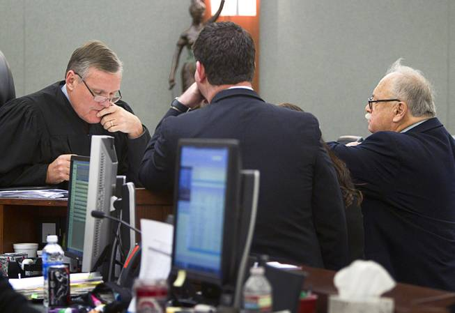 Judge David Barker confers with attorneys during an arraignment for pet shop owner Gloria Lee and co-defendant Kirk Bills at the Regional Justice Center Wednesday, March 12, 2014. Defense attorney Thomas Pitaro is at right. Lee and Bills pleaded not guilty to charges of torching the pet shop where 27 puppies were rescued, and a judge rejected a bid for lower bail.