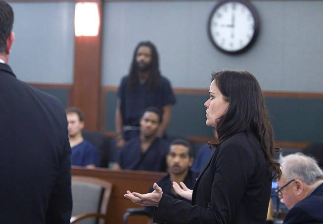 Prosecutor Shanon Clowers speaks to Judge David Barker during and arraignment for pet shop owner Gloria Lee and co-defendant Kirk Bills (standing, center) at the Regional Justice Center Wednesday, March 12, 2014. Lee and Bills pleaded not guilty to charges of torching the pet shop where 27 puppies were rescued, and a judge rejected a bid for lower bail.
