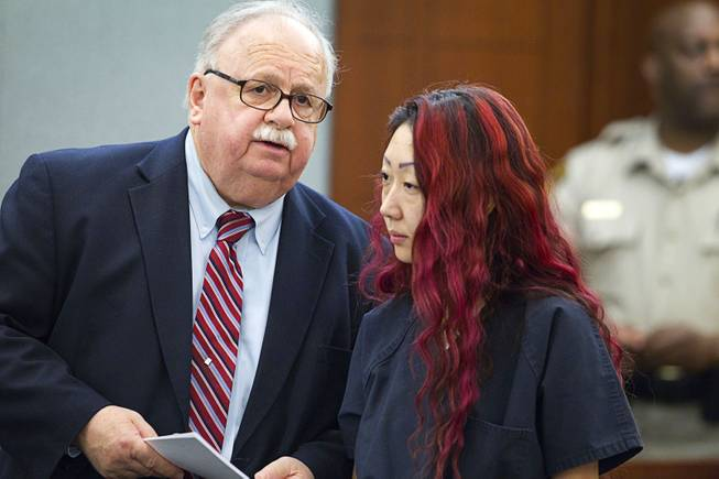 Defense attorney Thomas Pitaro speaks with pet shop owner Gloria Lee at the Regional Justice Center Wednesday, March 12, 2014. Lee and co-defendant Kirk Bills pleaded not guilty to charges of torching the pet shop where 27 puppies were rescued, and a judge rejected a bid for lower bail.