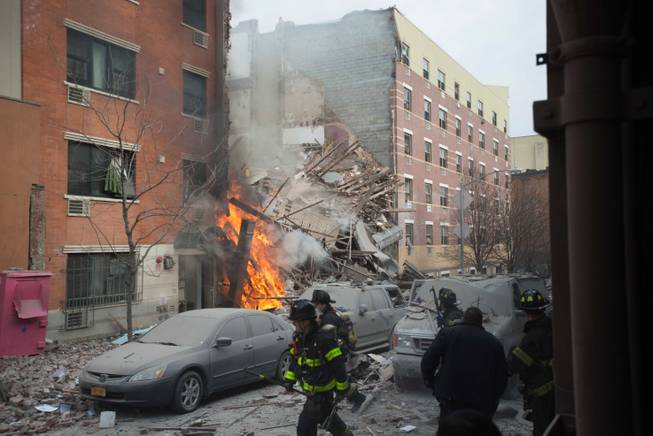 Firefighters work the scene of an explosion and building collapse in the East Harlem neighborhood of New York, Wednesday, March 12, 2014. The explosion leveled an apartment building, and sent flames and billowing black smoke above the skyline.