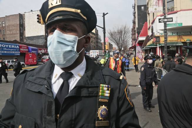 A police officers wear safety mask a block away from the site of an explosion that leveled two apartment buildings in the East Harlem neighborhood of New York, Wednesday, March 12, 2014. Con Edison spokesman Bob McGee says a resident from a building adjacent to the two that collapsed reported that he smelled gas inside his apartment, but thought the odor could be coming from outside.