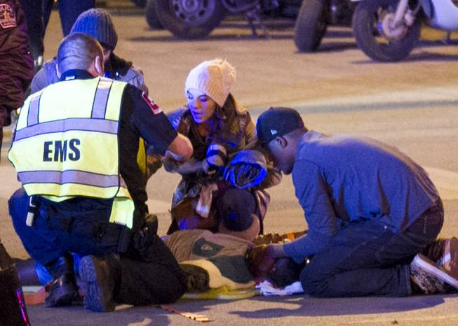 Bystanders and paramedics tend to a person who was struck by a vehicle on Red River Street in downtown Austin, Texas, at SXSW on Wednesday, March 12, 2014.  Police say a man and woman have been killed after a suspected drunken driver fleeing from arrest crashed through barricades set up for the South By Southwest festival and struck the pair and others on a crowded street.