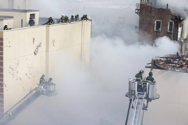 Firefighters respond to a fire after an explosion and building collapse in the East Harlem neighborhood of New York, Wednesday, March 12, 2014. The explosion leveled an apartment building, and sent flames and billowing black smoke above the skyline.