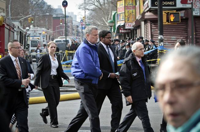 Mayor Bill de Blasio, center, arrives to visit the site of an explosion that leveled two apartment buildings in the East Harlem neighborhood of New York, Wednesday, March 12, 2014. Con Edison spokesman Bob McGee says a resident from a building adjacent to the two that collapsed reported that he smelled gas inside his apartment, but thought the odor could be coming from outside.