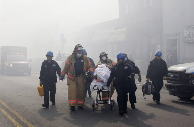 Rescue workers remove an injured person on a stretcher following a building explosion and collapse in East Harlem, Wednesday, March 12, 2014 in New York.