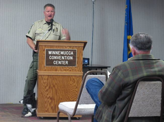 "Humboldt County Sherriff's Sgt. Chris Aker describes the county's drug interdiction program on U.S. Interstate 80 in Winnemucca, Nev., Tuesday, March 11, 2014, as his K-9 ""Boots'"" peers out from behind the podium during a public meeting at the Winnemucca Convention Center. About 40 people attended as Sheriff Ed Kilgore and others helped respond to questions about two federal lawsuits recently filed accusing county deputies of seizing tens of thousands of dollars without bringing criminal charges against suspected drug traffickers."