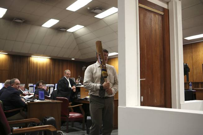 Forensic investigator Johannes Vermeulen, with a cricket bat in hand, demonstrates on a mock-up toilet and door details of how the door could have been broken down, during the trial of Oscar Pistorius in court during the second week of his trial in Pretoria, South Africa, Wednesday, March 12, 2014. Pistorius is charged with the shooting death of his girlfriend Reeva Steenkamp on Valentine's Day in 2013. At center back is prosecutor Gerrie Nel.