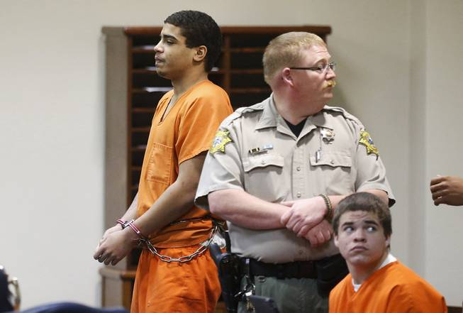 In this photo shot through a courtroom door, defendant Chancey Luna, left, is led from the courtroom following a hearing in Duncan, Okla., Wednesday, March 12, 2014. At right is defendant Michael Jones. Both are charged in the murder of Australian Christopher Lane.