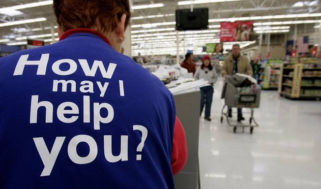 Customers at Wal-Mart head to the checkout lines past a worker with the company's motto on the back of her vest on Nov. 13, 2005, in Salt Lake City.