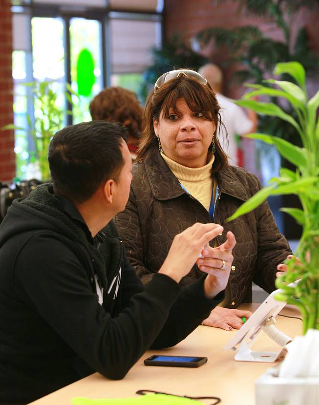 Ceci Walters assists Waldemer Morales in signing up for health insurance at the Nevada Health Co-Op Wednesday, March 12, 2014.