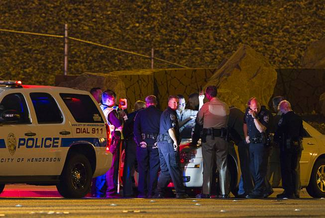 Law enforcement officers from Metro Police, Henderson Police and Nevada Highway Patrol confer near an accident site after a shooting victim was involved in an accident at the 1-215 eastbound off-ramp at Eastern Avenue Thursday, March 13, 2014. The driver, who had been shot multiple times, may have been shot at another location, police said.