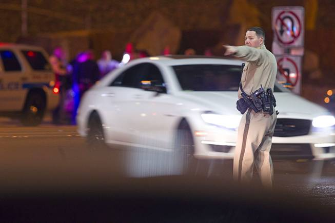 A Metro Police offer directs traffic after a shooting victim was involved in an accident at the 1-215 eastbound off-ramp at Eastern Avenue Thursday, March 13, 2014. The driver, who had been shot multiple times, may have been shot at another location, police said.