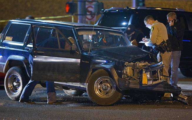 Metro Police investigators look over a vehicle after a shooting victim was involved in an accident at the 1-215 eastbound off-ramp at Eastern Avenue Thursday, March 13, 2014. The driver, who had been shot multiple times, may have been shot at another location, police said.