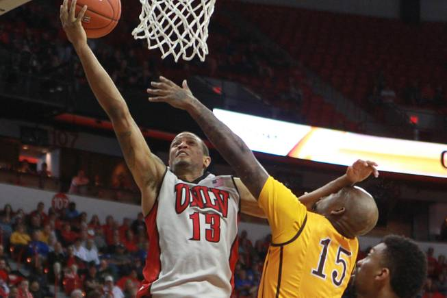 UNLV guard Bryce Dejean Jones drives to the basket while being defended by Wyoming guard Jerron Granberry during their Mountain West Conference tournament game Thursday, March 13, 2014 at the Thomas & Mack Center. UNLV won the game 71-67.