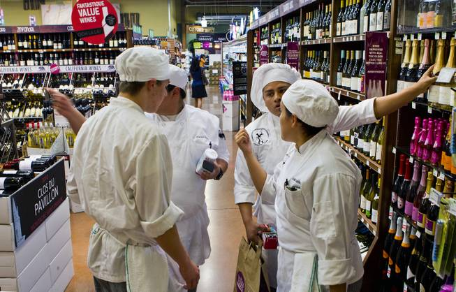 Students with the Southeast Career and Technical Academy consider which ingredients to select for their team to cook with during the Culinary Collision at the Whole Foods Market in Town Square on Thursday, March 13, 2014.