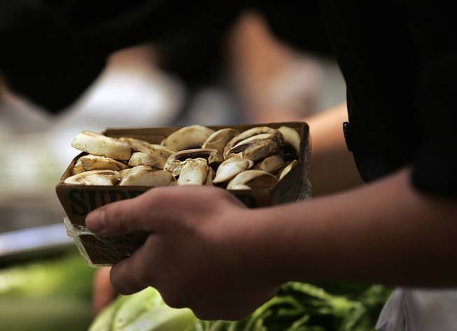 A student selects mushrooms as part of the meal her team is preparing during the Culinary Collision at the Whole Foods Market in Town Square on Thursday, March 13, 2014.