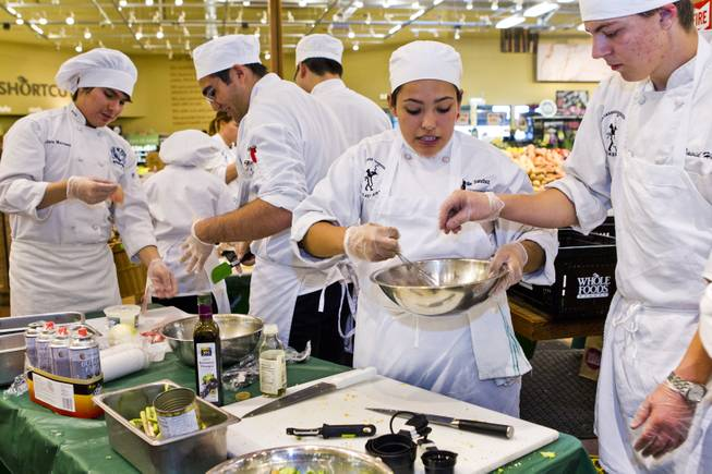 Students team up to prepare their selected meals during the Culinary Collision at the Whole Foods Market in Town Square on Thursday, March 13, 2014.