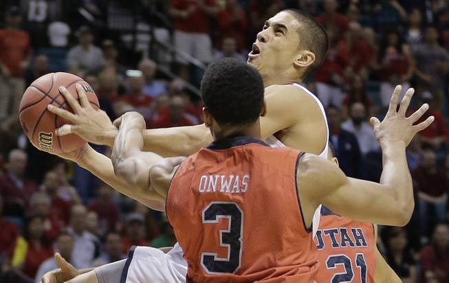 Arizona's Nick Johnson is fouled by Utah's Princeton Onwas (3) while shooting in the first half of an NCAA Pac-12 conference tournament college basketball game, Thursday, March 13, 2014, in Las Vegas.