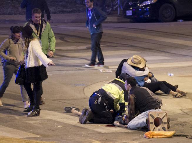 People perform CPR on a woman after she was struck by a vehicle on Red River Street in downtown Austin, Texas, at SXSW on Wednesday March 12, 2014. Police say a man and woman have been killed after a suspected drunken driver fleeing from arrest crashed through barricades set up for the South By Southwest festival and struck the pair and others on a crowded street.