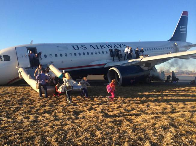 Passengers evacuate US Airways Flight 1702 after the pilot was forced to abort takeoff shortly after 6 p.m., after a tire on the plane's front landing gear blew out, Thursday, March 13, 2014, in Philadelphia.