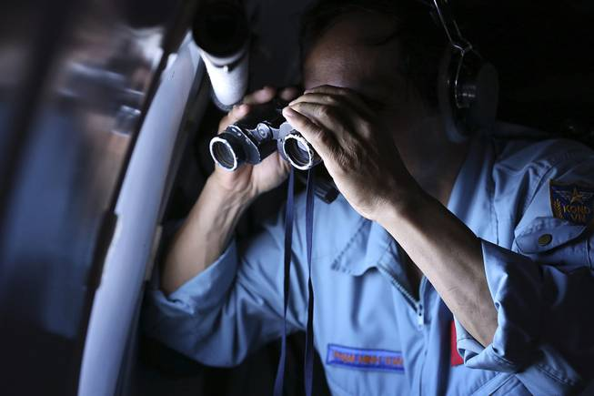 Vietnamese Air Force Col. Pham Minh Tuan uses binoculars on board a flying aircraft during a mission to search for the missing Malaysia Airlines flight MH370 in the Gulf of Thailand, Thursday, March 13, 2014.