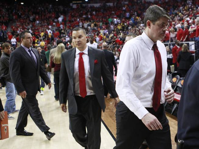 UNLV associate head coach Heath Schroyer, San Diego State assistant coach Justin Hutson and UNLV head coach Dave Rice exit the court after the Aztecs beat the Rebels 59-51 in their Mountain West Conference semifinal game Friday, March 14, 2014.
